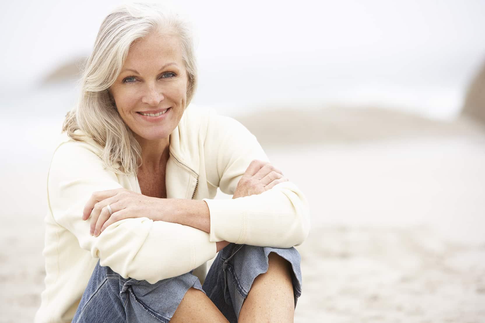 Senior Woman On Holiday Sitting On Winter Beach 2